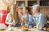 Lovely female family eating pastry and drinking milk at kitchen