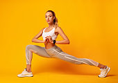 Girl Doing Deep Lunge Exercise Over Yellow Background