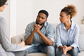 African American Couple Listening To Psychologist's Advice On Therapy Session
