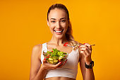 Fitness Girl Eating Vegetable Salad Standing Over Yellow Background