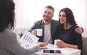 Young millennial couple enjoying coffee, listening to financial advisor