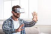 Man enjoyin virtual reality glasses at home