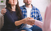 Thankful couple handshaking with specialist at counselor office