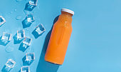 Orange and carrot detox water on blue background with ice