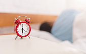 Man sleeping with alarm clock on foreground