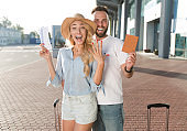 Excited newlyweds going on vacation and holding tickets at airport