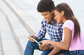 Young couple browsing social media on digital tablet outdoors