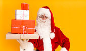 Santa Claus holding holiday gifts in hand on yellow