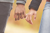 Young couple in love holding hands, walking through autumn park