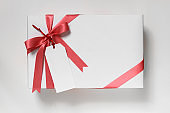White gift box with red ribbon and message card isolated on white background. Overhead view.