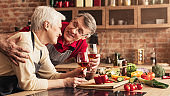 Senior couple in love relaxing with wine at kitchen