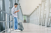Young passenger networking on cellphone at airport