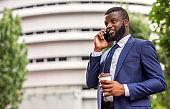 African American businessman talking on mobile phone during coffee break.