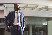 Successful African American businessman standing in front of office building