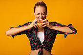 Sporty Girl Biting Burger On Yellow Background