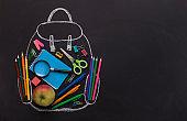 Modern backpack with school stationery inside on black board
