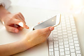 woman using smartphone at office desk