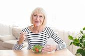 Happy senior lady eating fresh salad at home