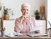 Smiling senior business woman working with documents at home