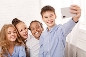 Happy schoolchildren taking selfie in light classroom