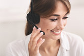 Smiling Girl In Headset Receiving Customer's Call Over White Background