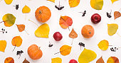 Autumn background with fallen leaves, pumpkin and red apples