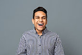 Portrait Of Positive Arab Guy Laughing Over Gray Background
