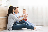 Adorable baby with parents sitting on floor at kitchen