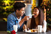 Young afro hipster feeding his girl cheesecake