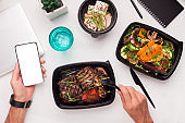 Man eating healthy food in to go boxes and holding cellphone