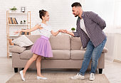 Little girl dancing with father, feeling like little princess