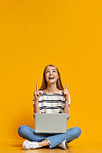 Excited teen girl with laptop pointing upwards at free space