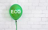 Eco green helium balloon with white text on bricks wall