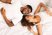 Young loving couple lying in bed together and looking at camera