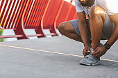African jogger checking on his shoelaces on bridge