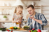 Dad and little daughter cooking in kitchen at home