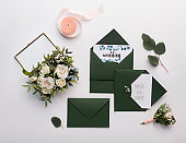 Stylish dark green envelopes with accessories on white