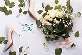 Flat lay of bridal bouquet and high heel shoes on white