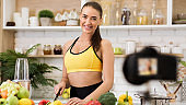 Sport blogger cooking salad for new vlog, recording video