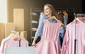 Dreamy blonde girl trying on pink dress at clothing store