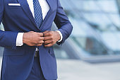 African American Businessman Buttoning Up Jacket In City, Cropped