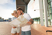 Excited couple using map, planning route for vacations