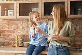 Happy mother and daughter drinking tea at kitchen