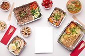 Delivery of healthy food in foil boxes to go on white