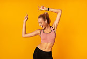Woman In Wireless Earphones Dancing Listening To Music, Yellow Background