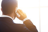 Businessman talking on phone, consulting clients, back view