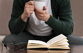 Caucasian man reading book and drinking coffee at home