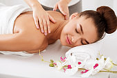 Woman enjoying shoulder massage, relaxing with closed eyes