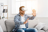 Young man with virtual reality headset playing video game