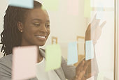 Happy Businesswoman Reading Notes On Visualization Board Standing In Office